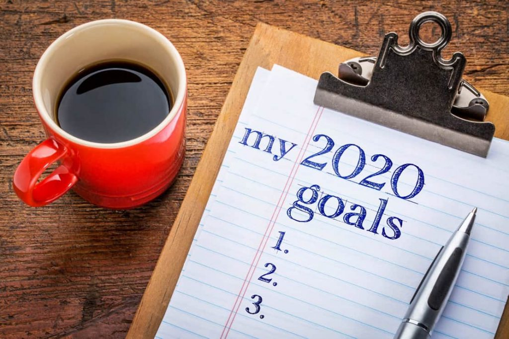 Coffee and paper and pen on a table, paper reads 'my 2020 goals'