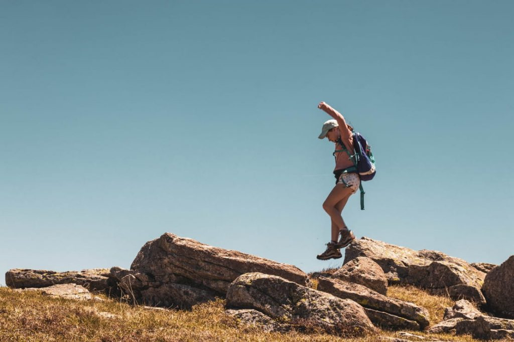 Woman balancing over rocky hurdles on a hike.
