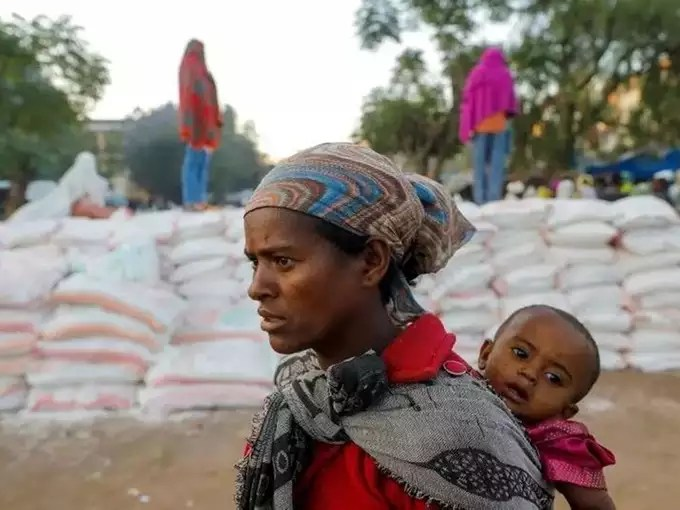 FILE PHOTO_ Woman carries an infant as she queues in line for food, at the Tsehaye primary school, in Shire.