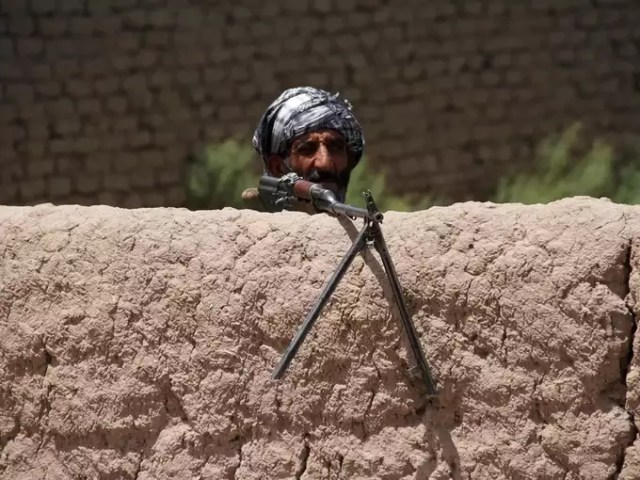 Former Mujahideen keeps watch at a check post as he holds a weapon to support Afghan forces in their fight against Taliban, on the outskirts of Herat province.