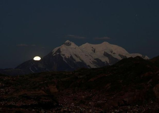 The moon rises behind the Illimani mountain during a lunar eclipse complete in La Paz, Bolivia, July 27, 2018.