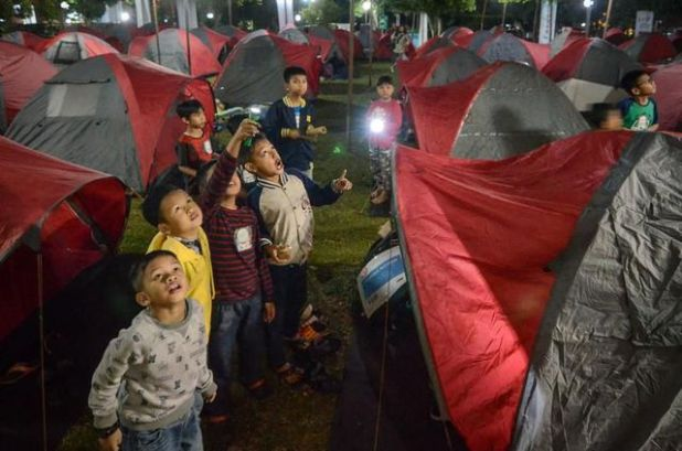Indonesian children watch the blood moon, waiting for the lunar eclipse at Salman Astro camp in Bandung, Indonesia.