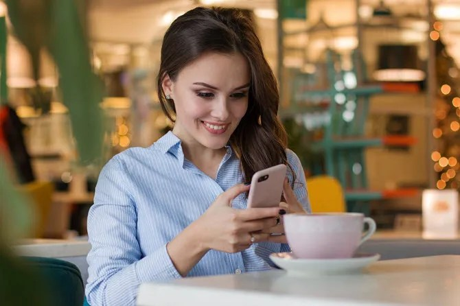 girl smiling while using her phone
