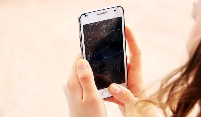 A woman holding a broken smartphone