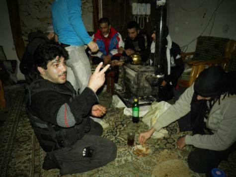 Combattants de l'armée syrienne libre prenant une pause autour d'un poêle à bois