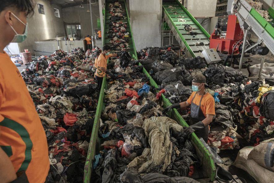 Trabalhadores colocam em esteiras o lixo plástico que será lavado e triturado na unidade de reciclagem da Re>Pal em Pasuruan, região leste de Java. A unidade recicla sacolas plásticas, embalagens plásticas e alguns tipos de embalagens de alimentos, transformando-as em paletes plásticos com capacidade para até uma tonelada.