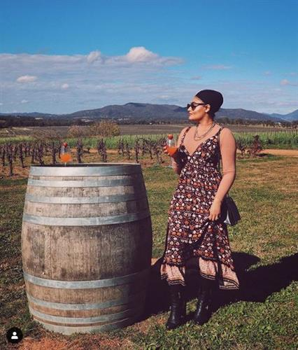 Modest fashion influencer Karen Kaur wearing a long-sleeve bodysuit with a dress and boots while enjoying a glass of wine in a vineyard