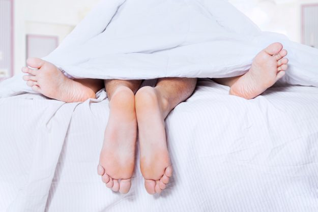 Close-up of couple's feet having intimate relation in bed