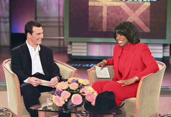 Oprah on her show in the red suit
