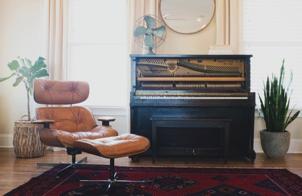 Black Upright Piano Near Orange Glider Chair