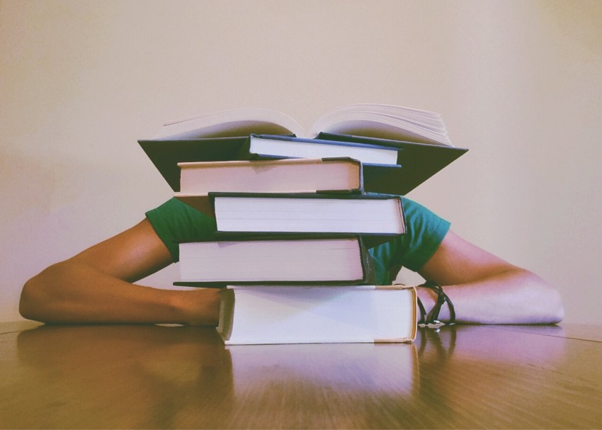 A student sits behind a pile of textbooks.