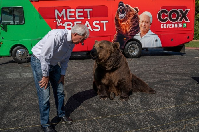 """John Cox begins his statewide """"Meet the Beast"""" bus tour on Tuesday, May 4, 2021, with Tag, a Kodiak brown bear."""