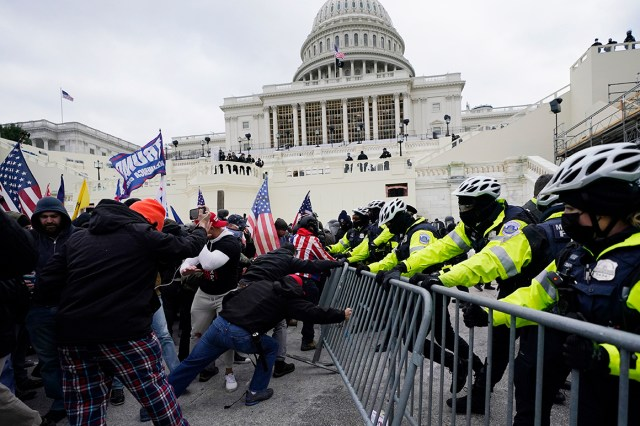 Rioters try to break through a police barrier Jan. 6 at the Capitol in Washington.