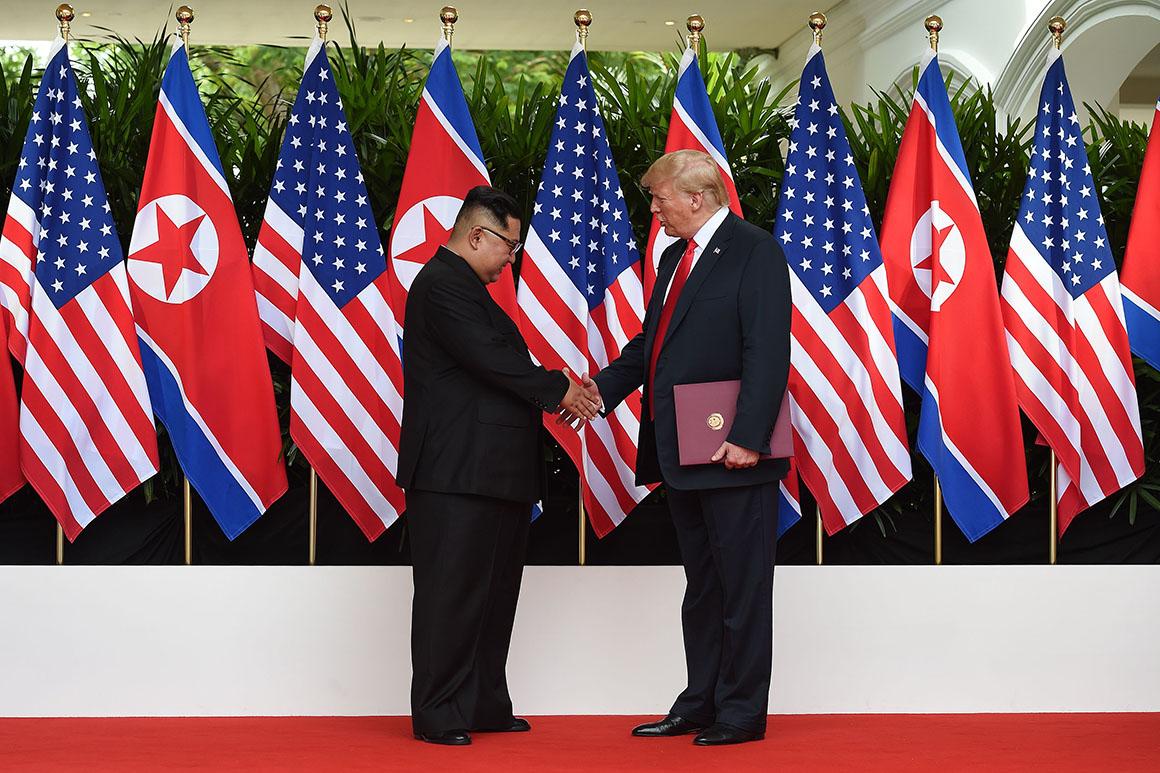 Donald Trump and Kim Jong Un shake hands.