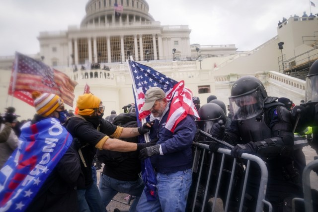Rioters try to break through a police barrier at the Capitol in Washington.