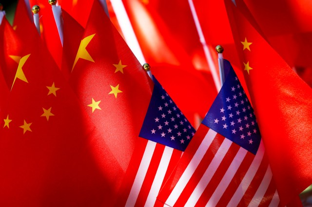A number of Chinese flags surround a few American flags