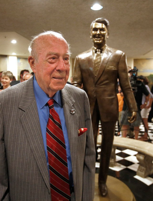 George Shultz poses by a statue of his former boss, President Ronald Reagan, that was unveiled at the Capitol in Sacramento, California, on June 22, 2015.
