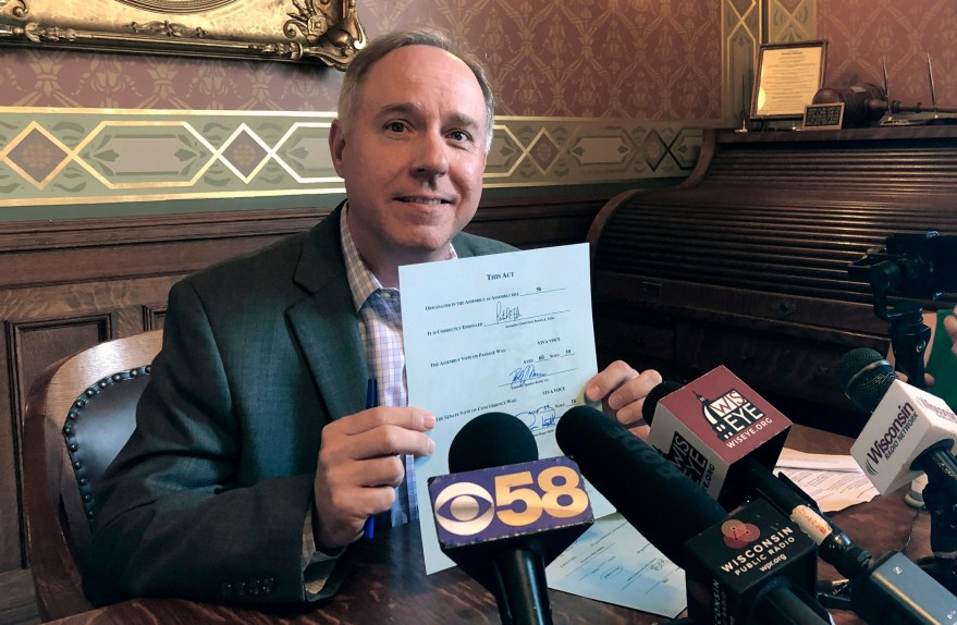 Wisconsin Assembly Speaker Robin Vos shows off his signature on the state budget after signing the spending plan in his state Capitol office.