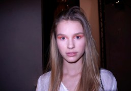 A young model in sweet orange make-up backstage at the Vanessa Bruno…