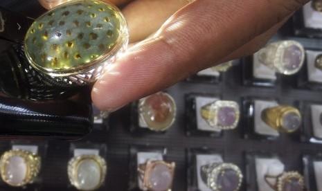 Penjual memeriksa salah satu cincin batu mulia yang dipasarkan di salah satu stan di Mangga Dua Square, Jakarta, Jumat (19/9).  (Antara/Martha Herlinawati Simanjuntak)