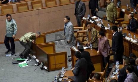 Ketua Fraksi PPP Hasrul Azwar (kiri) meninggalkan ruang rapat usai membalik meja rapat saat rapat paripurna terkait pengesahan alat kelengkapan dewan (AKD) di Gedung Nusantara II, DPR, Jakarta, Selasa (28/10).  (Republika/Agung Supriyanto)