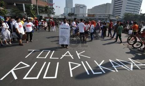 Aktivis yang tergabung dalam Koalisi Kawal RUU Pilkada melakukan aksi tolak RUU Pilkada di kawasan Bundaran Hotel Indonesia, Jakarta, Ahad (14/9).  (Republika/ Tahta Aidilla)