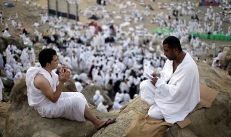 Jamaah haji memanjatkan doa di bukit Jabal Rahmah saat melaksanakan ibadah wukuf di Arafah, Senin (14/10).  (AP/Amr Nabil)
