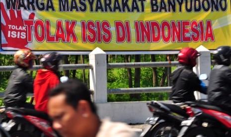 Pengendara motor melintas di dekat spanduk himbauan menolak ISIS yang terpasang di pinggir jalan Solo-Boyolali, Jawa Tengah, Kamis (2/4).