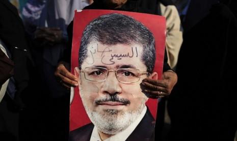 Pengunjuk rasa memegang foto Presiden Muhammad Mursi di Nasser City, Kairo, Mesir, Kamis (4/7).    (AP/Hassan Ammar)