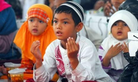 Sejumlah anak yatim piatu khusuk berdoa saat mengikuti acara