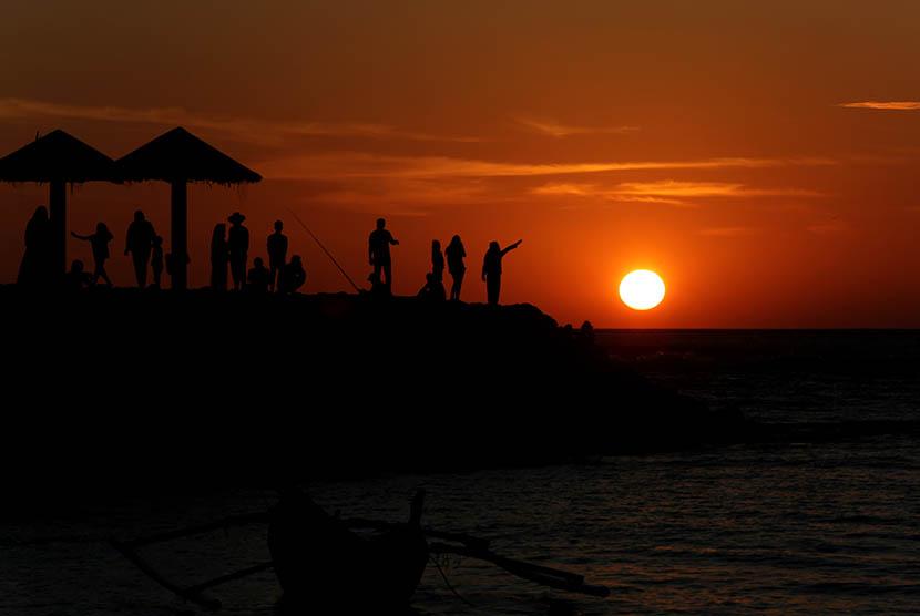 Warga menikmati matahari terbenam (sunset) pada hari akhir tahun 2015 di pantai Lampuuk, Kecamatan Lhoknga, Kabupaten Aceh Besar, Aceh, Kamis (31/12).  (Antara/Irwansyah Putra)