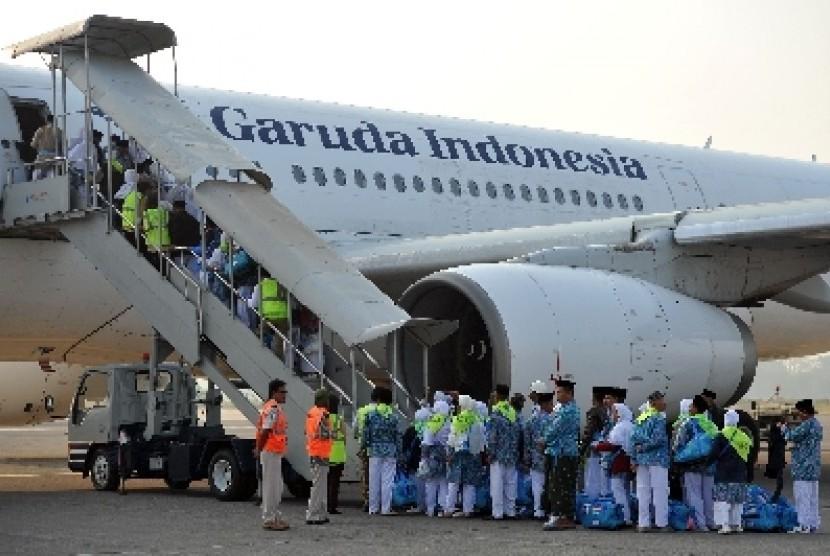 Calon jamaah haji kloter pertama embarkasi Solo menaiki pesawat maskapai Garuda Indonesia untuk diterbangkan ke Jeddah, Arab Saudi, di Bandara Adi Soemarmo, Solo,