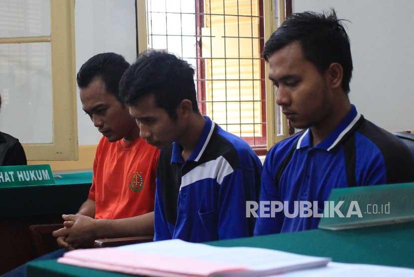 Ketiga terdakwa kasus pembunuhan sekeluarga Andi Lala (kiri), Andi Syahputra (tengah) dan Roni Anggara (kanan) mengikuti sidang dengan agenda tuntutan di Pengadilan Negeri Medan, Sumatera Utara, Jumat (29/12).