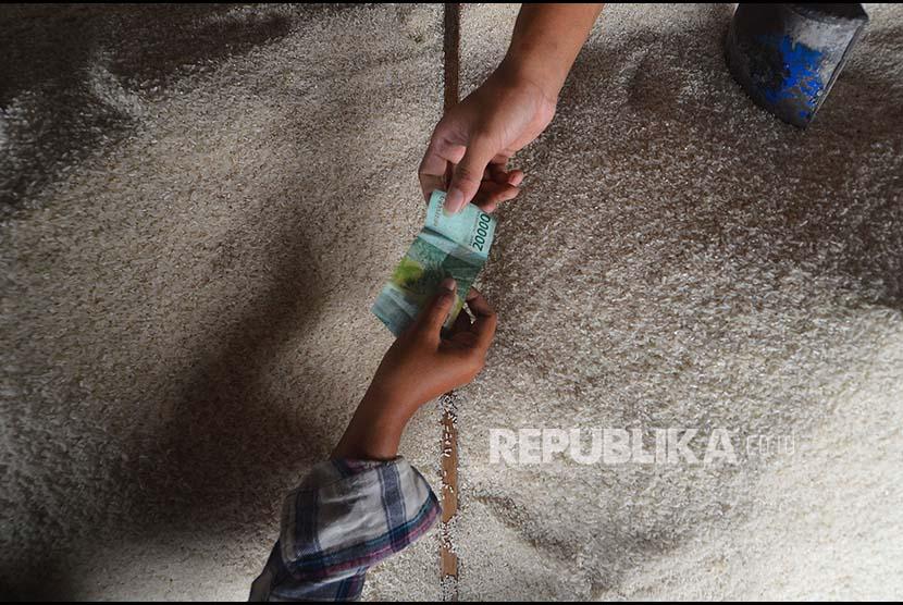 Pedagang beras melayani pembeli di Pasar Tradisional Cikurubuk, Kota Tasikmalaya, Jawa Barat, Senin (4/9). Sejumlah pedagang belum mengetahui kebijakan Peraturan Menteri Perdagangan (Permendag) terkait penetapan Harga Eceran Tertinggi (HET) untuk beras medium dan beras premium wilayah Jawa, Lampung, Sumatera Selatan, Bali, Nusa Tenggara Barat, dan Sulawesi dengan harga sebesar Rp9.450 per kilogram dan Rp12.800 per kilogram.