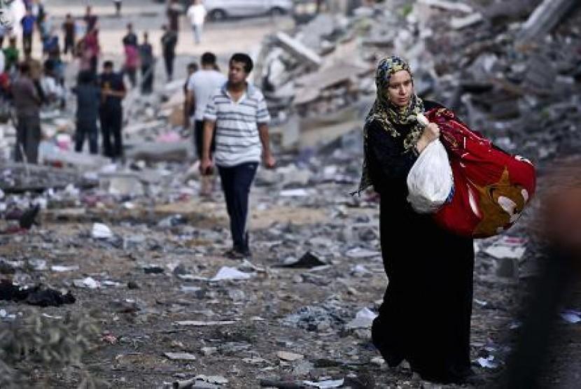 Perempuan Palestina membawa barang di tengah reruntuhan gedung di Jalur Gaza.