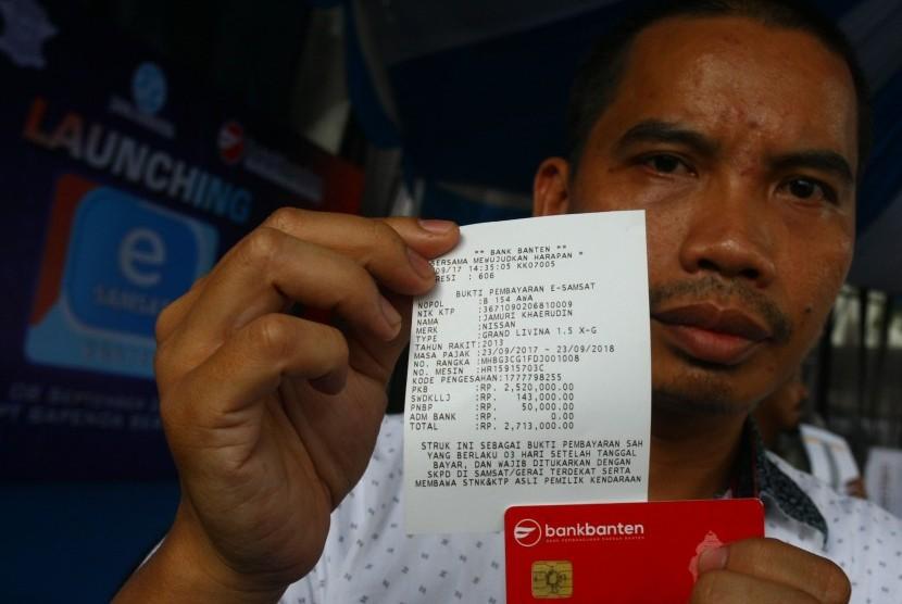 Seorang wajib pajak menunjukan bukti transaksi pembayaran pajak kendaraan bermotor (PKB) yang dibayarkan secara online seusai peluncuran E- Samsat di Serpong, Tangerang Selatan, Banten, Jumat (8/9).