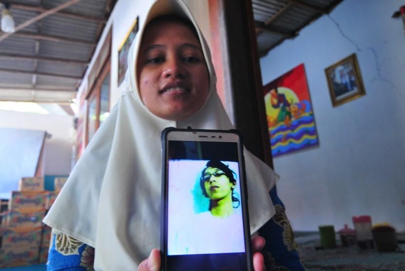 Sianit Sinta menujukkan foto mendiang suaminya Ahmad Budi Cahyanto guru SMAN 1 Torjun yang tewas dipukul siswanya sendiri, di Desa Tanggumung, Sampang, Jawa Timur, Sabtu (3/2).