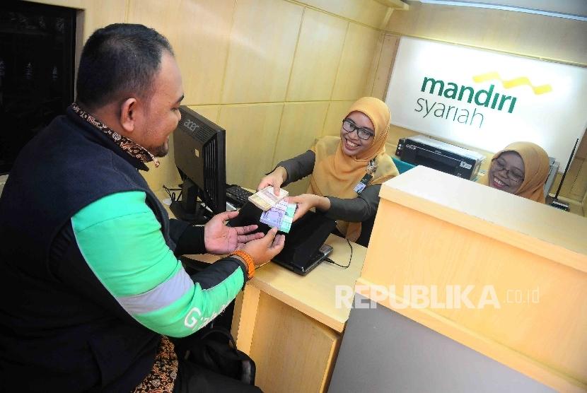 Warga menukarkan uang pecahan kecil di mobil kas kelilinga Bank Syariah Mandiri (BSM) di IRTI Monas, Jakarta, Senin (20/6).