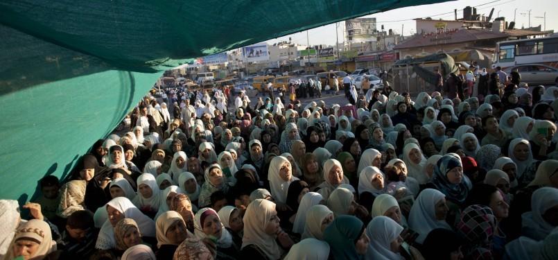 Warga Tepi Barat, Palestina, menunggu untuk melewati pos penyeberangan Qalandia dalam perjalanan menuju Masjid Al Aqsa untuk beribadah.
