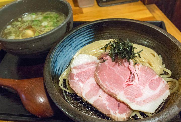 大阪市谷町近隣で屈指の人気を誇る、行列ラーメン店がこちら。安心安全な素材と自家製麺にこだわり、身体に優しいメニューを提供しています。ここのつけ麺は大阪ではまだまだ珍しい淡麗系の塩味で、鶏と魚介の旨味が生きた優しく沁み渡るような味わいが特徴的。それなのに物足りなさを感じさせず、きちんとつけ麺のスープとして成立させているのはお見事。更にこれが自慢の麺の旨さを最大限に引き立てており、思った以上にスルスルっと食べられちゃいますよ。その麺は、中盛りまで無料で増量可能なのも嬉しいところ。