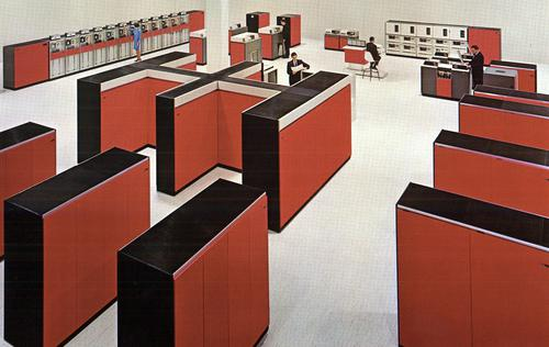 Large computer room with an IBM System/360 Model 85. The CPU, the double-H unit in the center, weighed over 7 tons. Cabinets in front are core memory storage, holding 256 kilobytes each. Cabinets on the right are I/O channels, connected to I/O devices at the back: tape drives, printers, disk drives, and card readers. Photo from IBM.