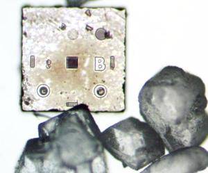Photo of a two-diode silicon die next to sugar crystals. This photo is a composite of top-lighting to show the die details, with back-lighting to show the sugar.