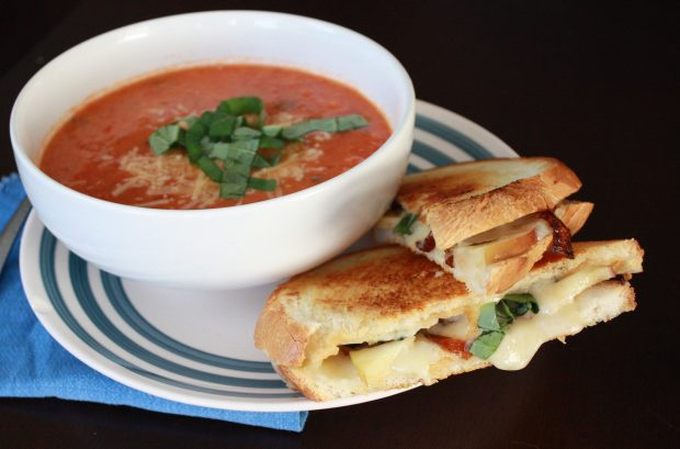 Tomato soup with sliced basil paired with a cheddar, apple, basil and caramelized onion grilled cheese.