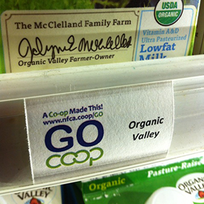A sign that reads Go Co-op placed in front of an Organic Valley milk package.