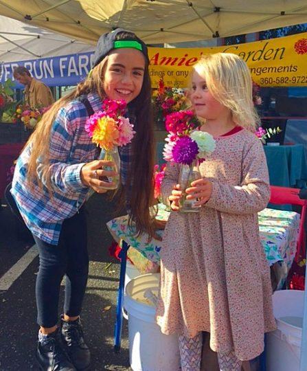 Two young girls hold multi-colored zinnias at a farmers market.