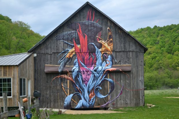 Aaron Horkey's completed Farm Art mural depicts a prehistoric creature rising from red and blue flames, symbolizing a warning of what will remain if we do not cooperate amongst ourselves and with our shared earth.