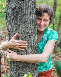 Melinda Hemmelgarn hugging a tree.