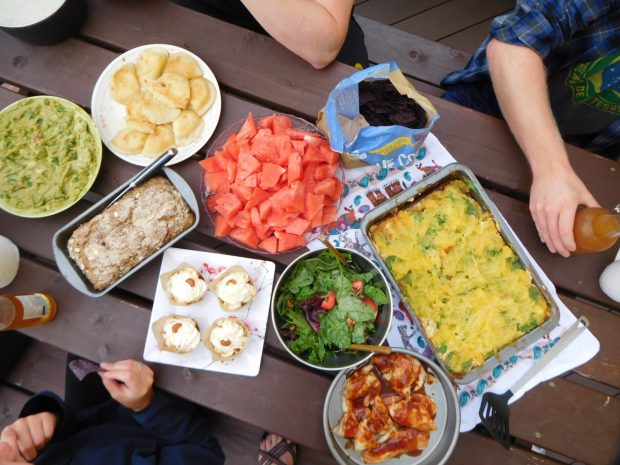 Picnic table filled with potluck dishes