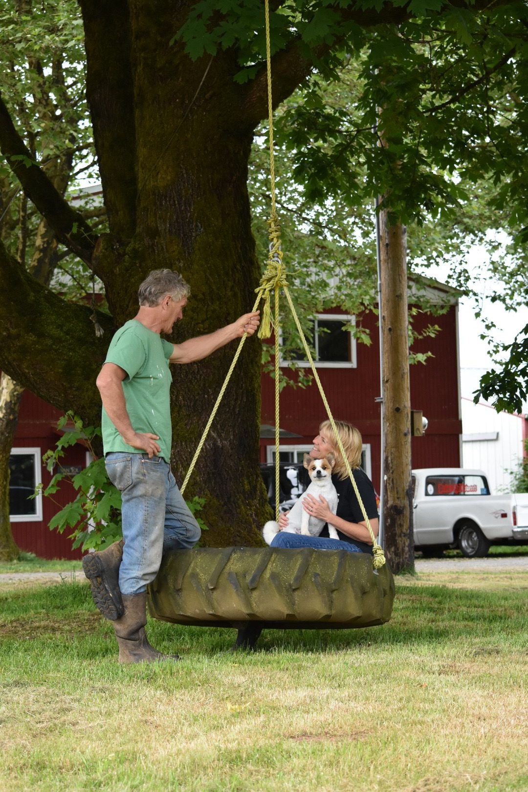 Karen van Tol holds their dog while sitting in a tire swing talking to Gerrit.