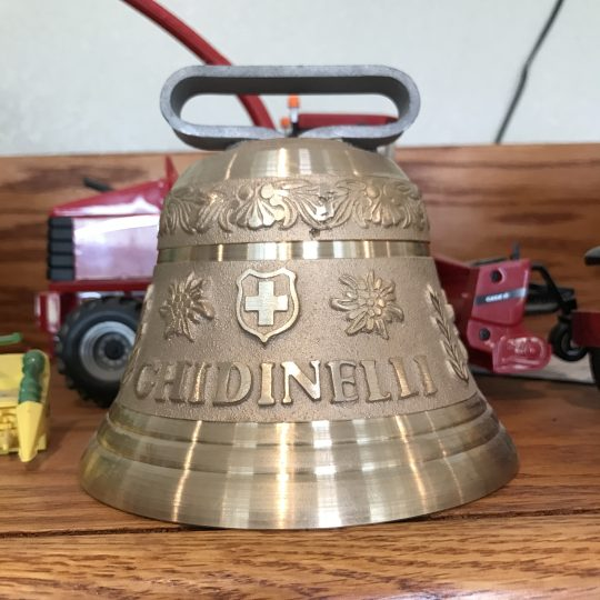A large cowbell with the Ghidinelli name and crest engraved on it.